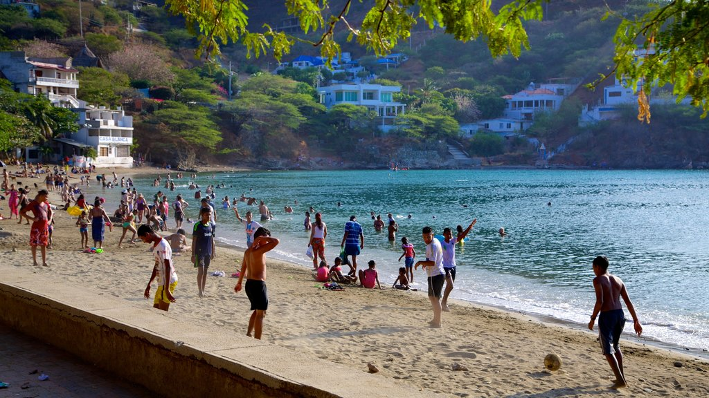 Taganga Beach which includes a coastal town, swimming and a sandy beach