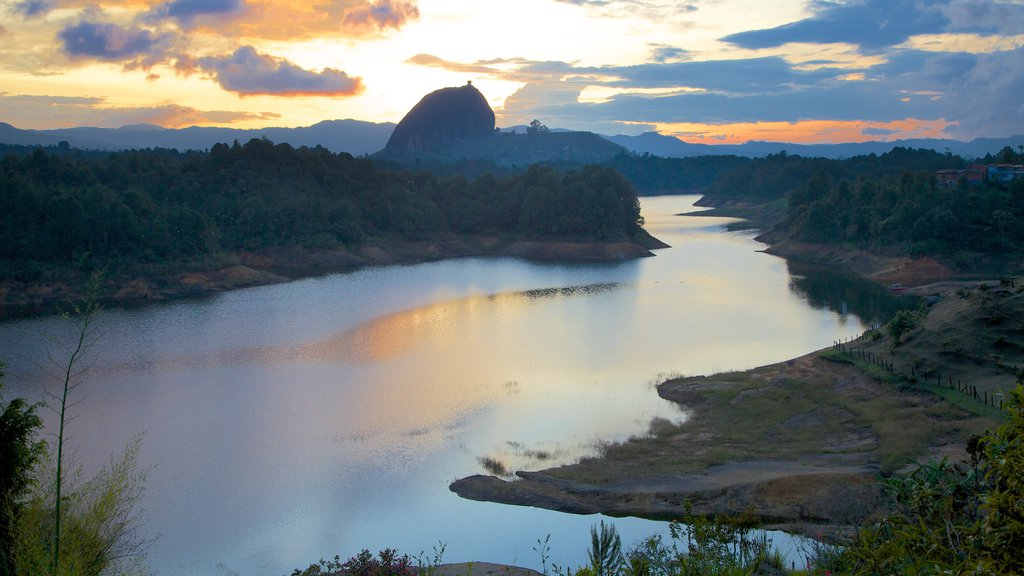Rock of Guatape which includes a sunset, landscape views and forest scenes