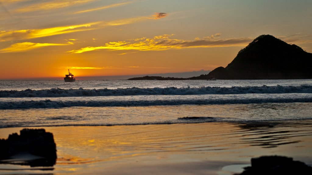 Nicaragua featuring a sunset, rocky coastline and surf