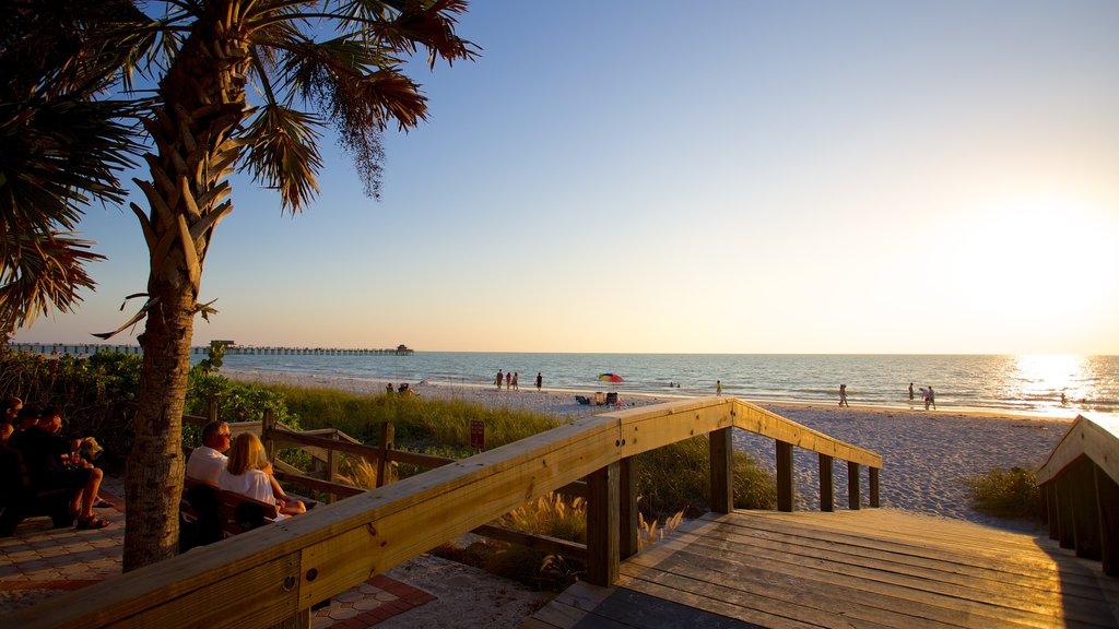 Naples que incluye una puesta de sol y una playa de arena