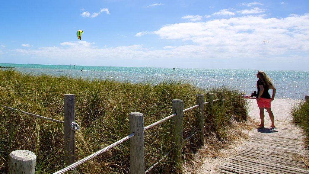 Smathers Beach featuring a sandy beach and a bridge as well as an individual femail