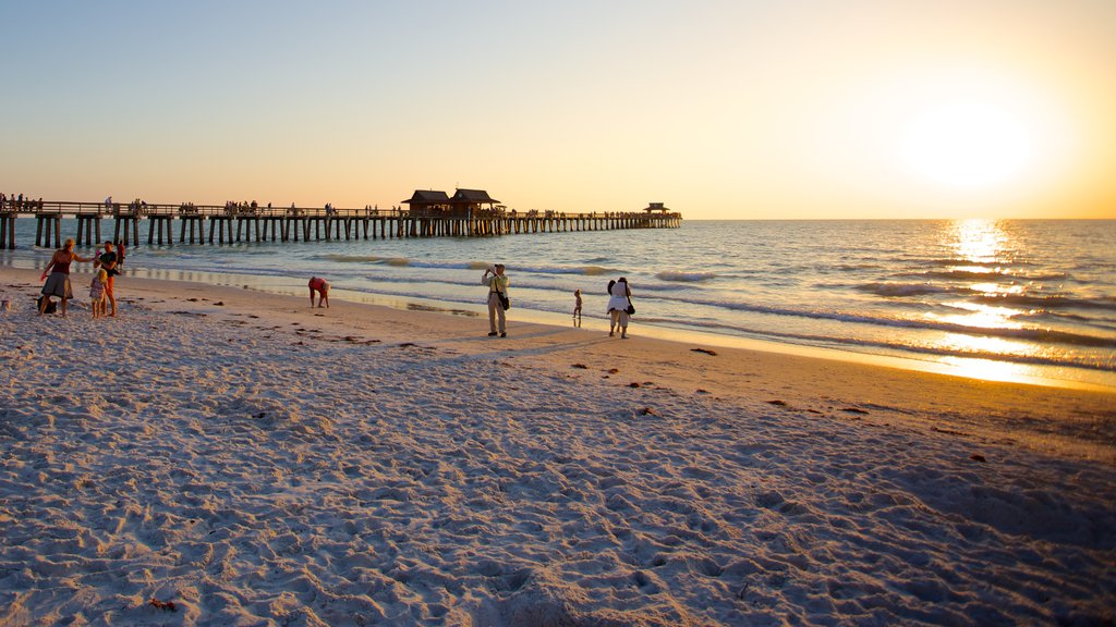 Naples Pier which includes a sunset and a sandy beach