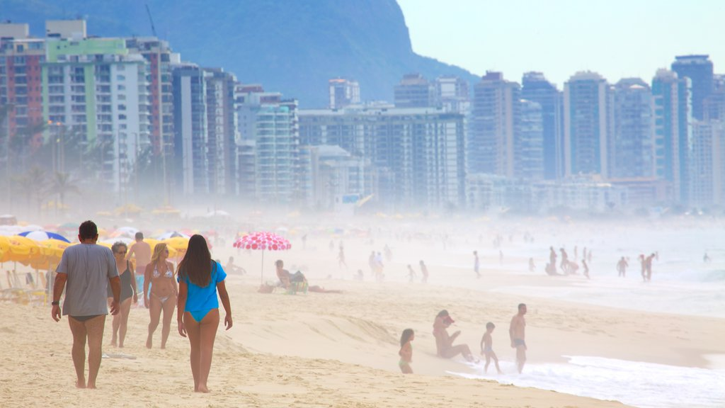 Barra da Tijuca which includes a sandy beach and mist or fog as well as a large group of people