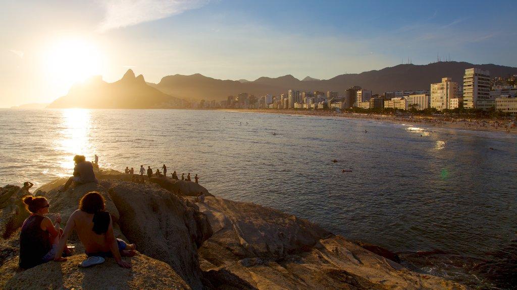 Playa de Arpoador que incluye una puesta de sol y vistas generales de la costa
