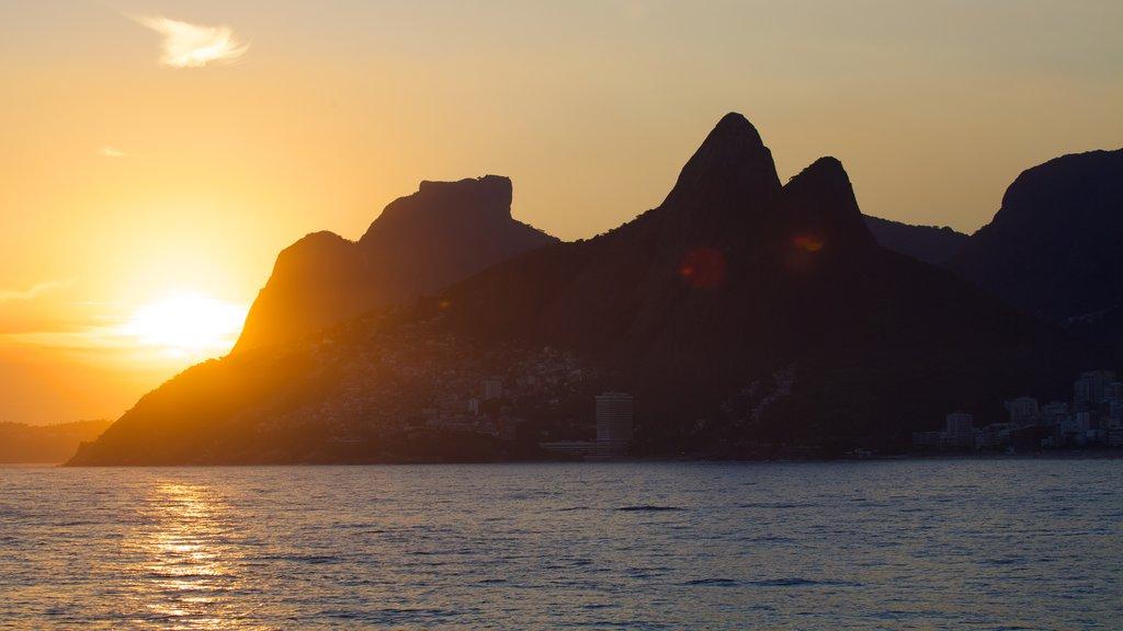 Playa de Arpoador que incluye montañas, una puesta de sol y vistas generales de la costa