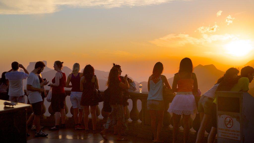 Corcovado mostrando paisagens e um pôr do sol assim como um grande grupo de pessoas