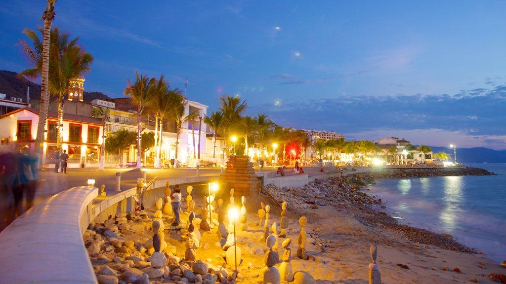 Malecón ofreciendo escenas nocturnas, una ciudad costera y una playa de arena