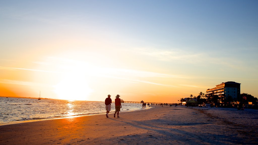 Fort Myers Beach which includes a sandy beach and a sunset as well as a small group of people