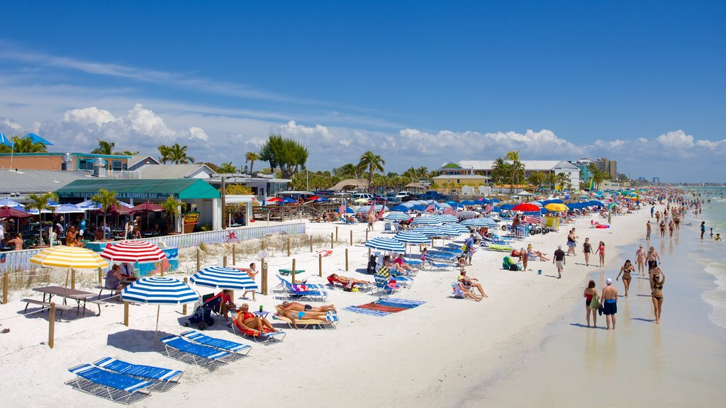 Fort Myers Beach featuring a luxury hotel or resort and a sandy beach as well as a large group of people