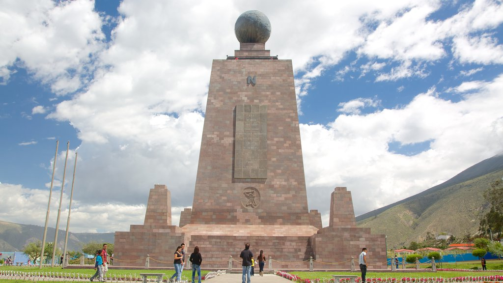 Mitad del Mundo Monument which includes a monument and a park as well as a large group of people
