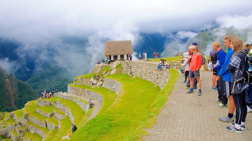 Machu Picchu caracterizando uma ruína e escalada ou caminhada assim como um grande grupo de pessoas