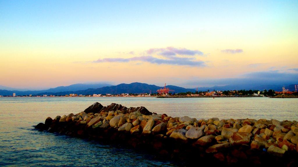 Playa San Pedrito featuring rugged coastline, a sunset and general coastal views