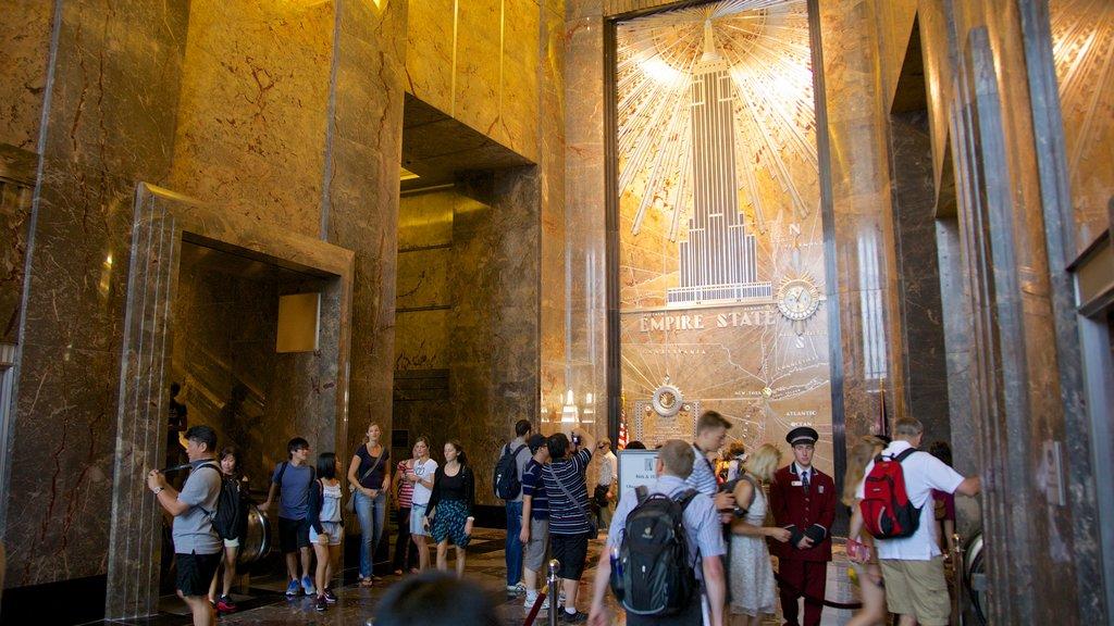 Edificio Empire State que incluye vistas interiores y también un gran grupo de personas