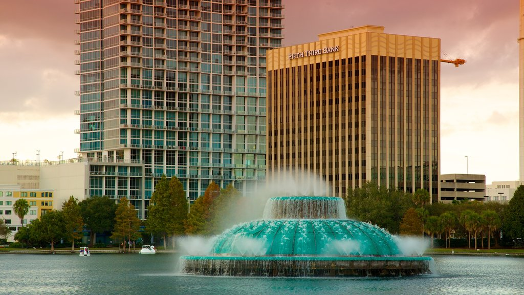 Lake Eola Park which includes a sunset, a lake or waterhole and a city
