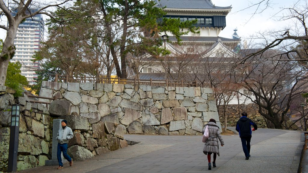 Kokura Castle featuring street scenes as well as a small group of people