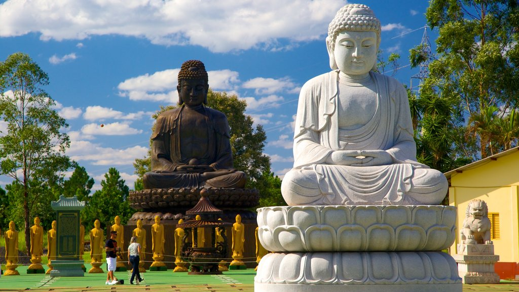Buddhist Temple which includes a statue or sculpture, a temple or place of worship and religious aspects