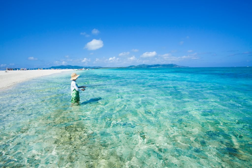 Woman fishing on coral sand cay