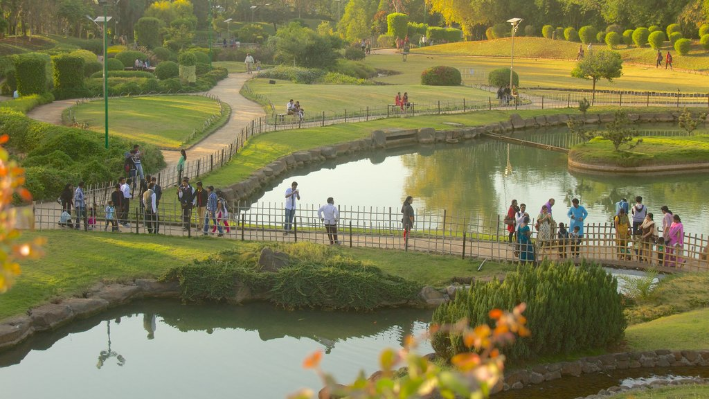 Pune featuring a lake or waterhole and a garden as well as a large group of people