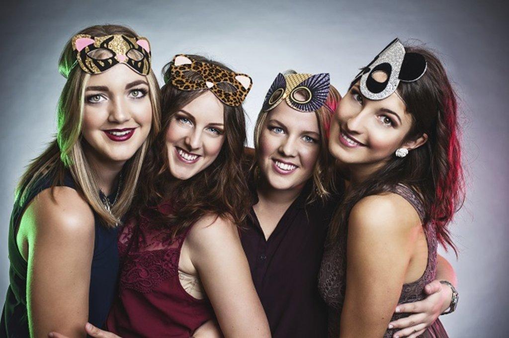 A group of friends wearing fancy dress masks