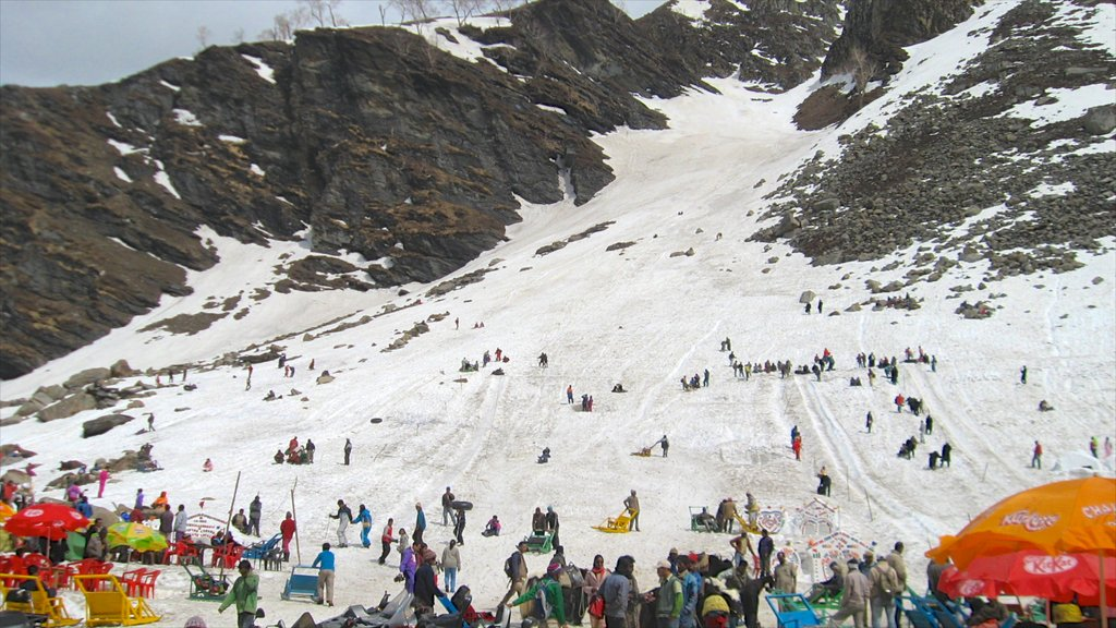 Manali which includes snow and mountains as well as a large group of people