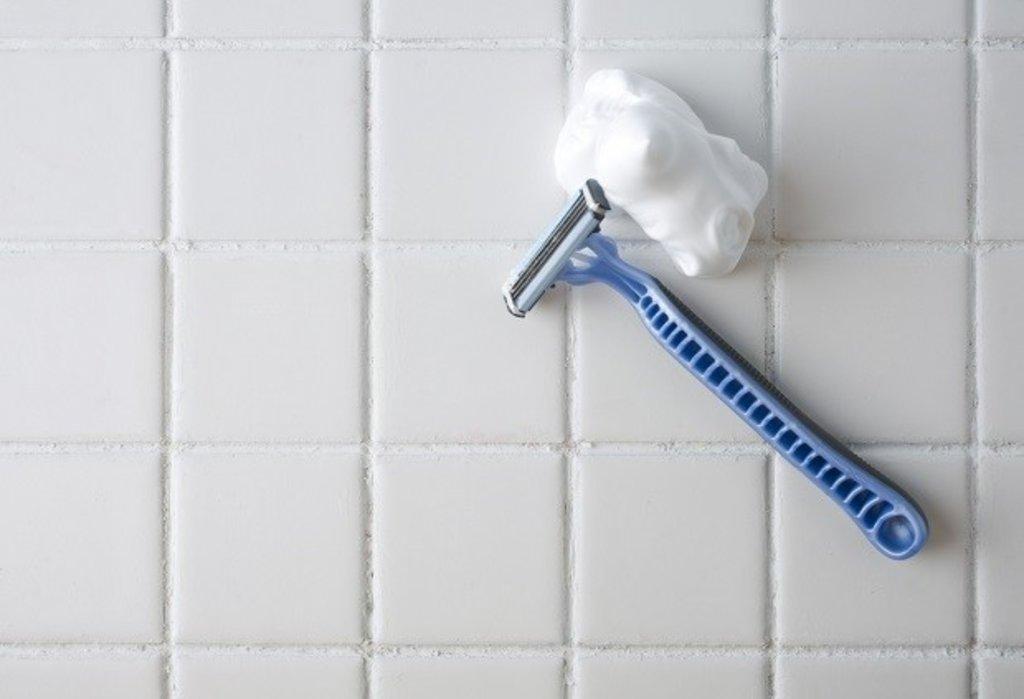 Razor and shaving foam in bathroom
