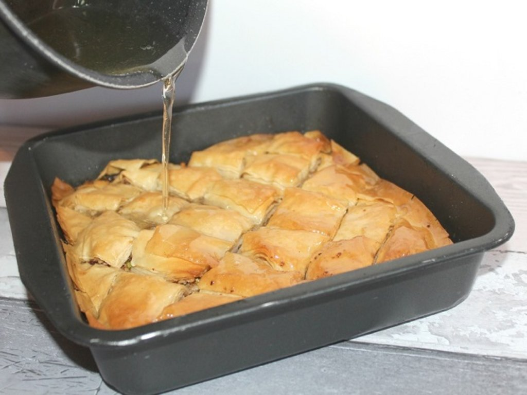Syrup being poured over a tray of baklava