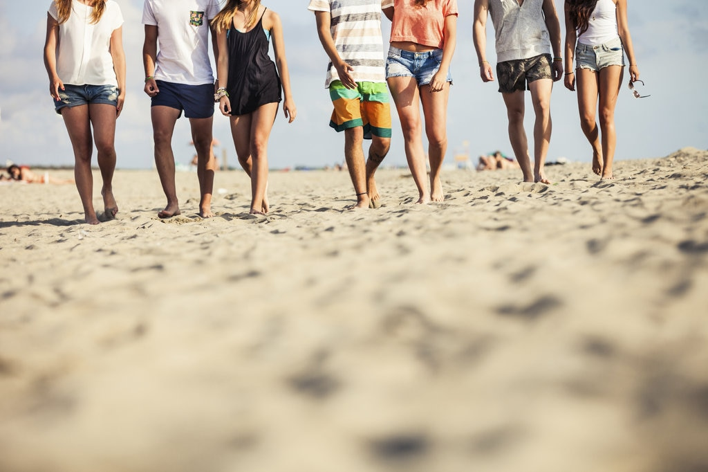 Group of men and women walking on the beach