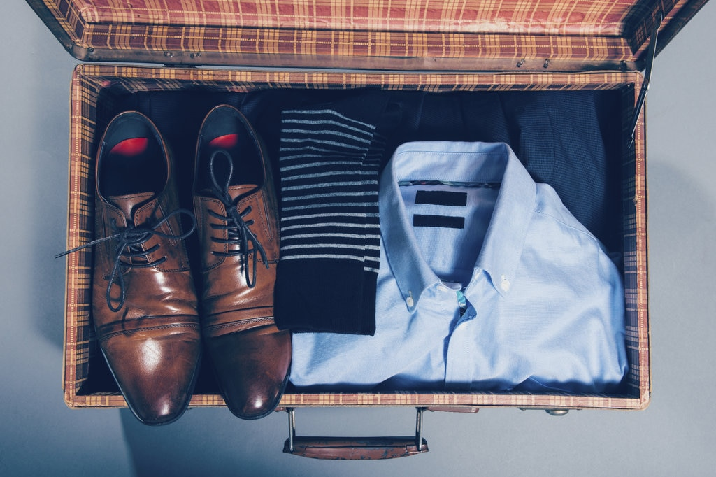 Open suitcase with men's clothing