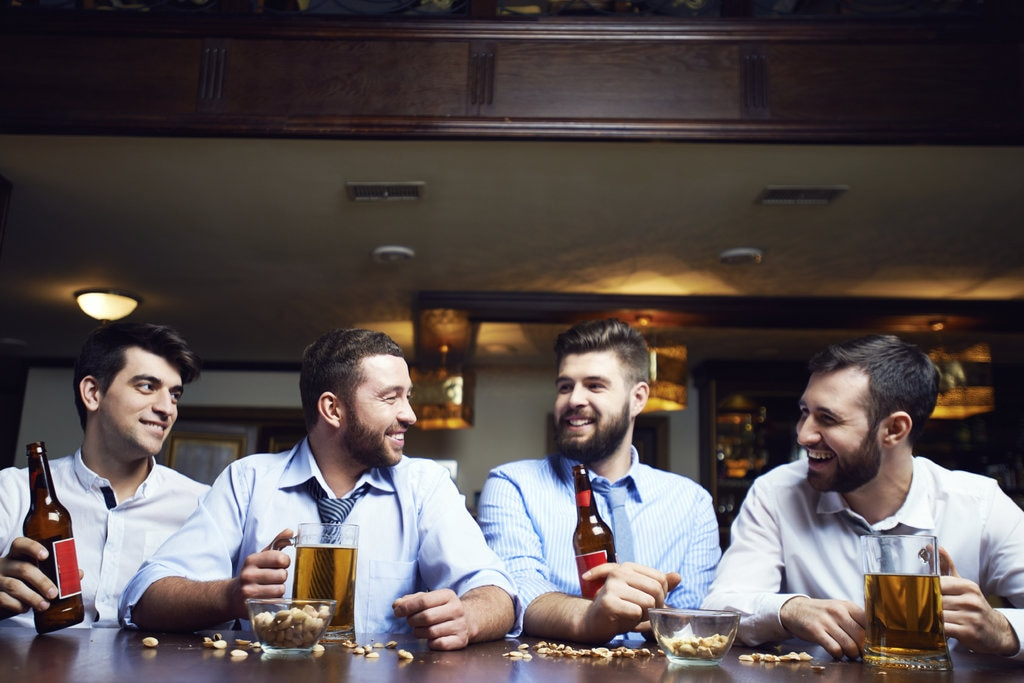 Group of men drinking beers and laughing in same outfits