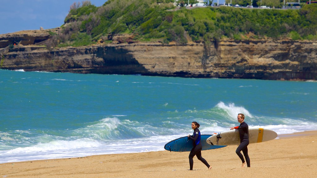 Grand Beach showing a sandy beach, rocky coastline and surfing
