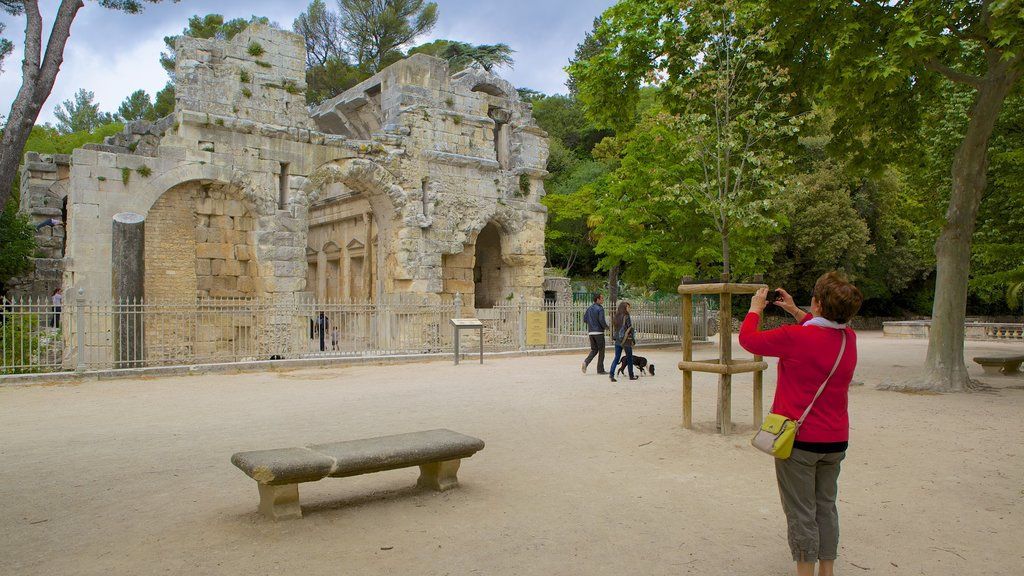 Nimes showing heritage architecture and building ruins as well as an individual femail