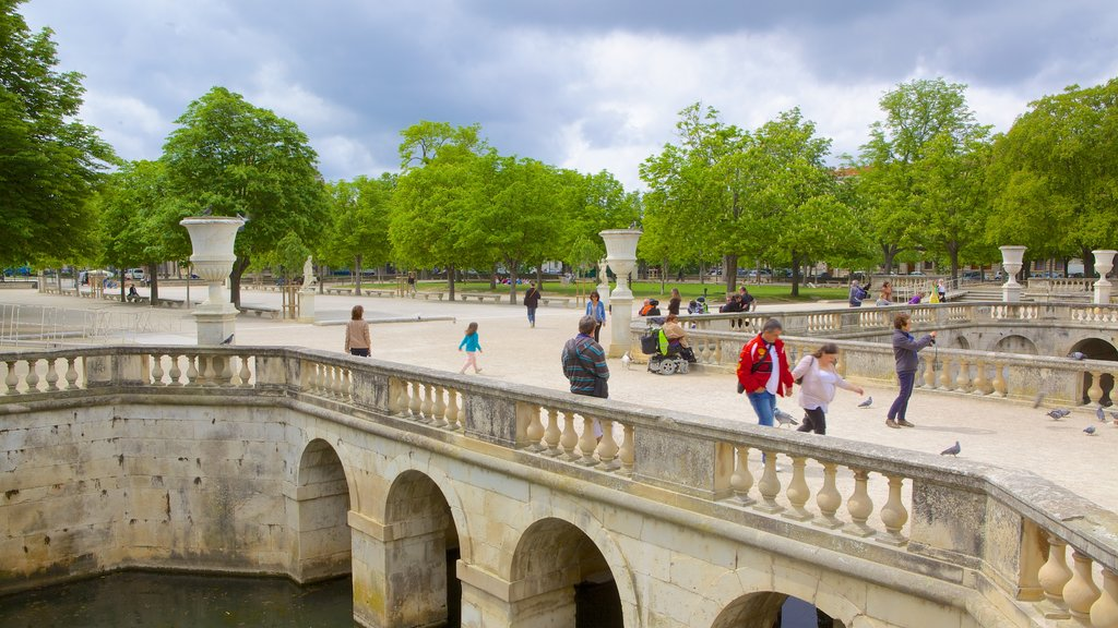 Nimes featuring a river or creek as well as a large group of people
