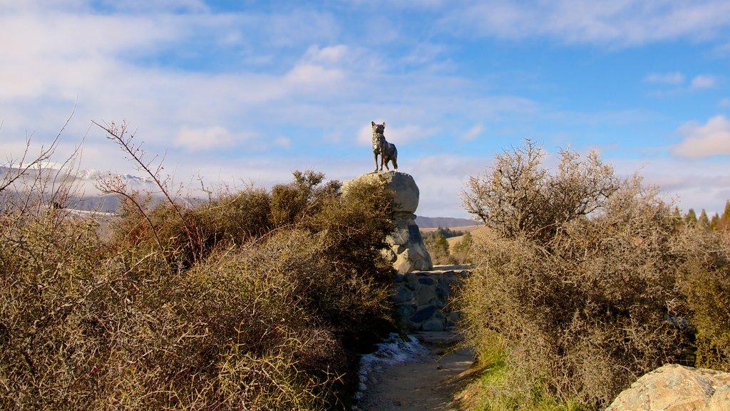 Estatua del perro pastor que incluye tierras de cultivo y arte al aire libre