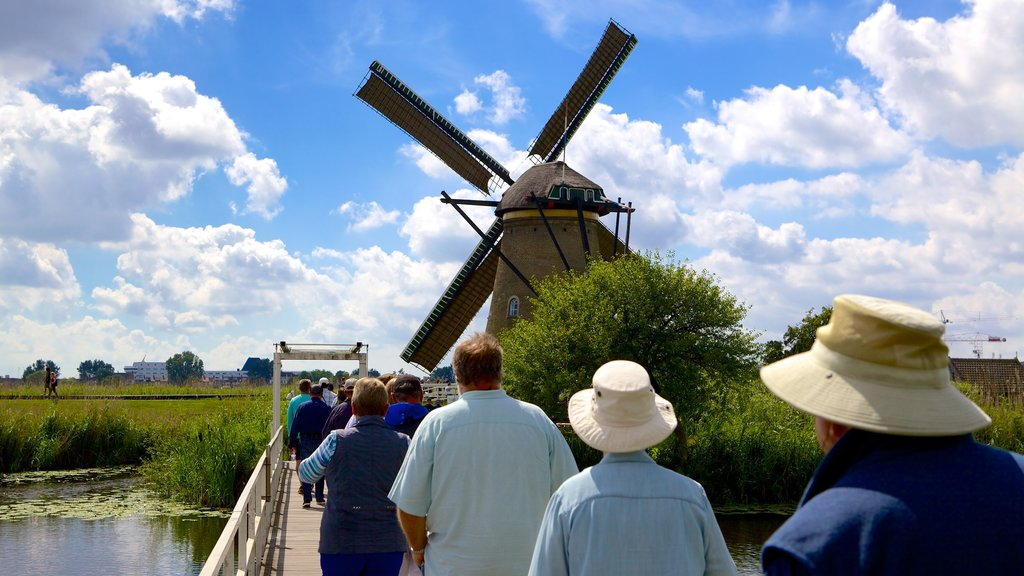 Kinderdijk featuring a windmill and wetlands as well as a large group of people