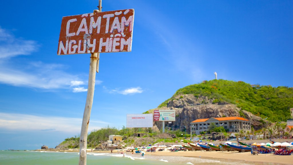 Back Beach showing signage and a sandy beach