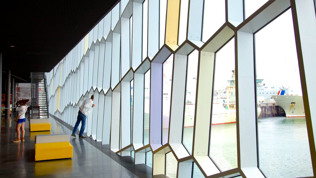 Harpa featuring interior views and modern architecture as well as a small group of people