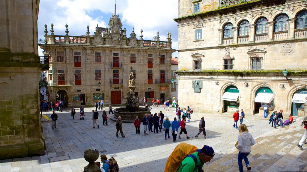 Santiago de Compostela Cathedral which includes a fountain and a square or plaza as well as a large group of people