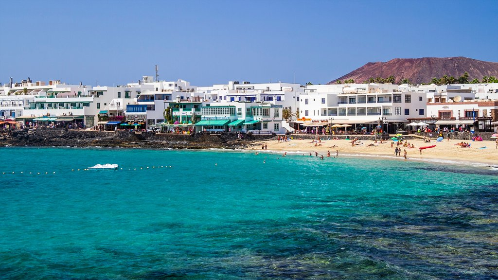 Lanzarote showing a coastal town, a sandy beach and a luxury hotel or resort
