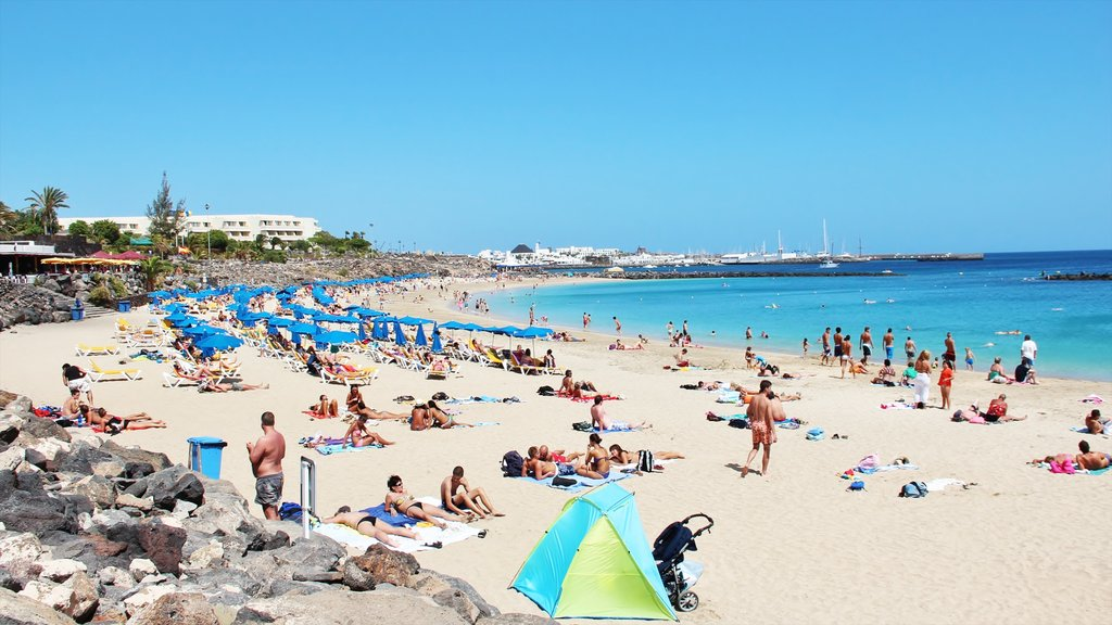 Lanzarote featuring a sandy beach as well as a large group of people