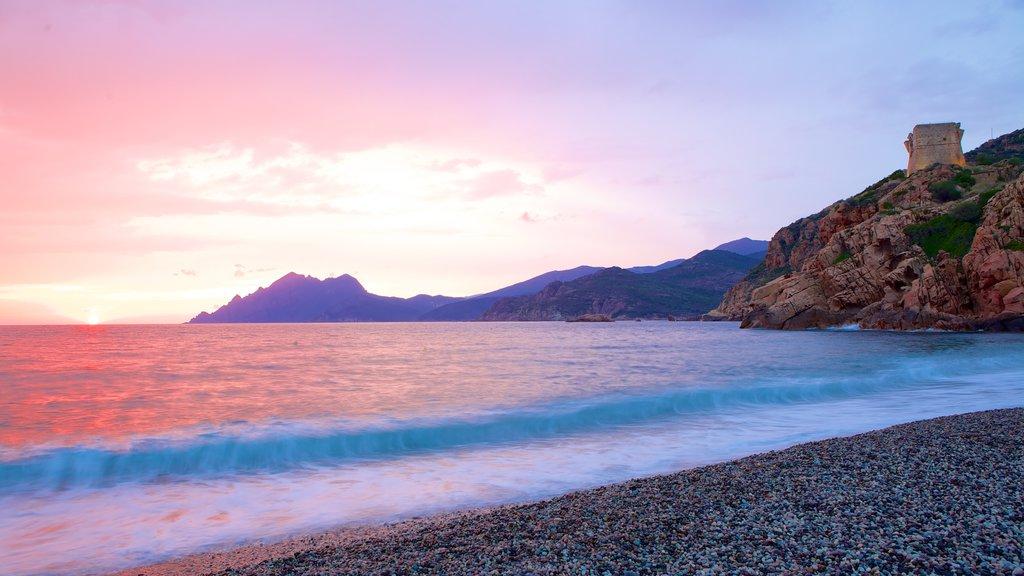 Torre de Genoese que incluye una puesta de sol y una playa de guijarros