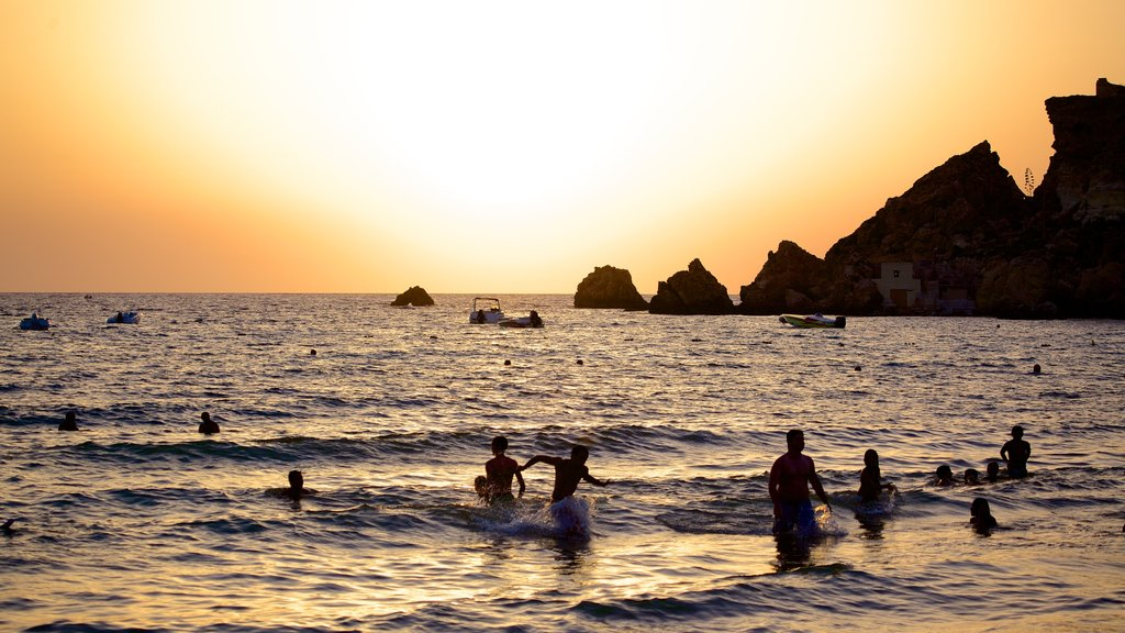 Golden Sands Beach which includes swimming, general coastal views and a sunset