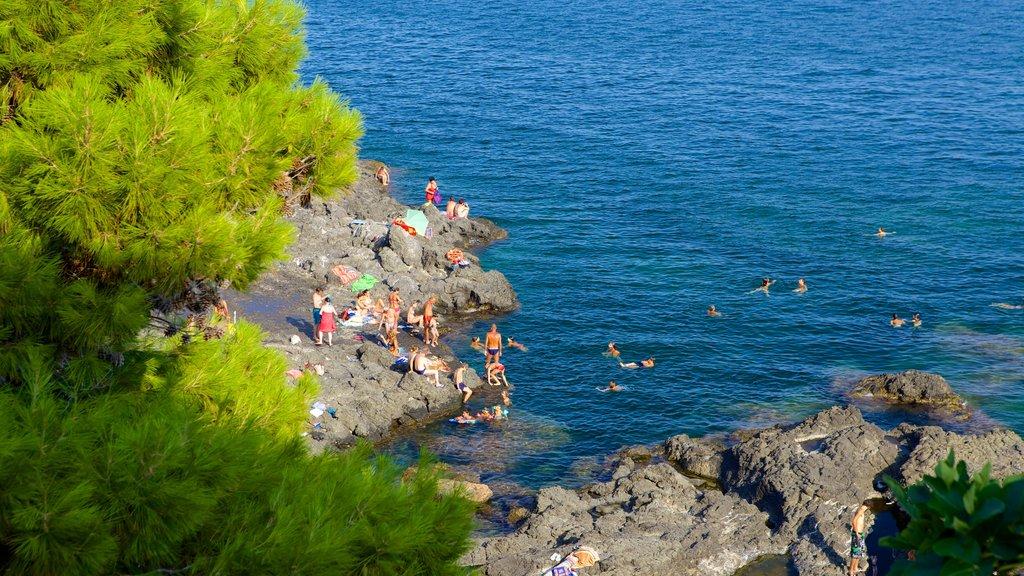 Aci Castello mostrando costa escarpada y natación