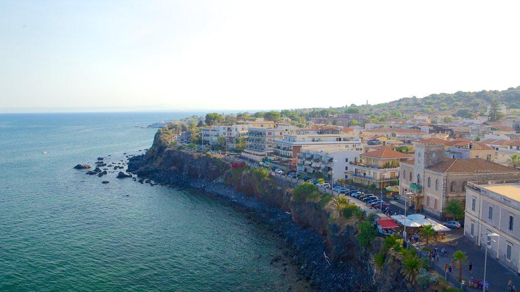Aci Castello mostrando costa rocosa y una ciudad costera