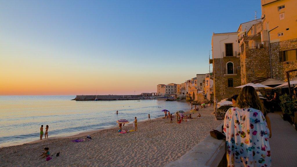 Cefaù mostrando una ciudad costera, natación y una puesta de sol