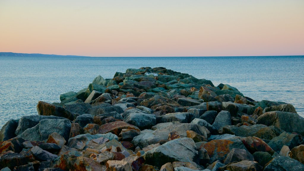 Noosa Beach featuring rocky coastline and a sunset