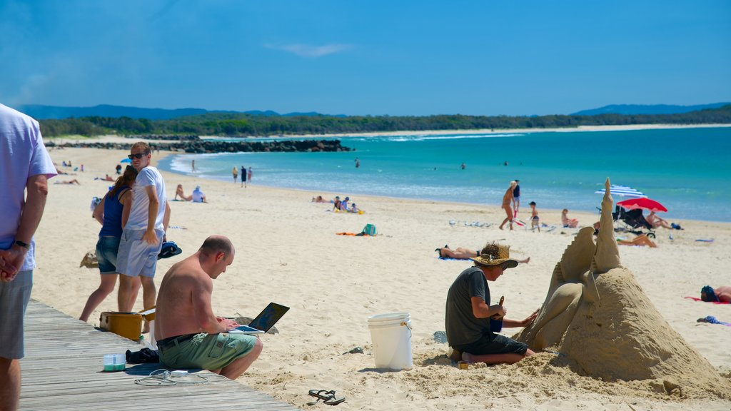 Noosa Beach showing outdoor art and a sandy beach as well as a large group of people