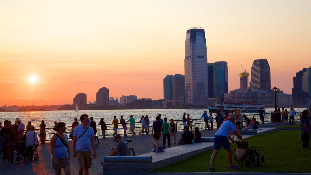 Battery Park showing a sunset, a city and a bay or harbor