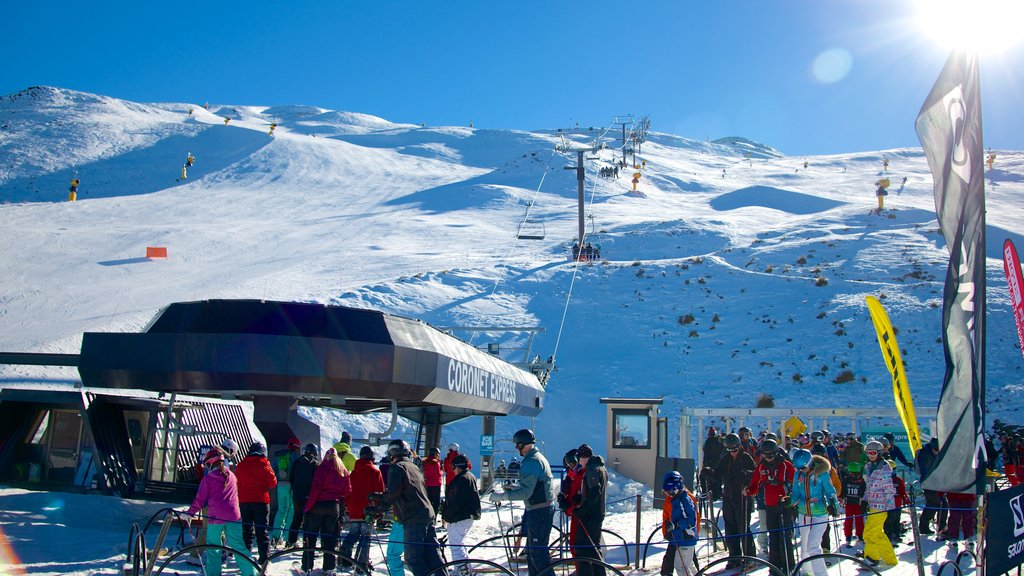 Coronet Peak Ski Area showing snow as well as a large group of people