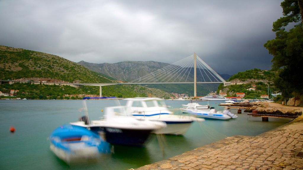 Lapad Beach featuring mountains, boating and a bridge