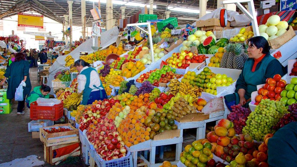 Mercado de San Pedro de Cusco que incluye mercados y comida y también un pequeño grupo de personas